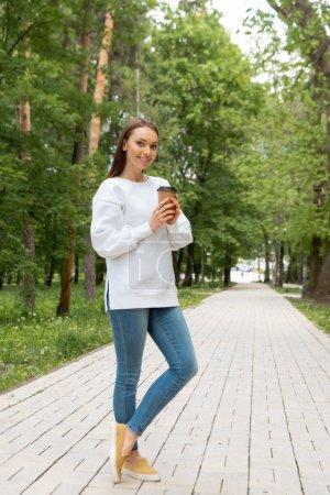 Photo pour Heureuse jeune femme tenant du café pour aller dans une tasse en papier tout en se tenant dans le parc - image libre de droit
