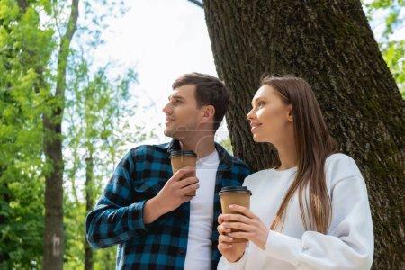 Photo pour Heureux couple tenant des tasses en papier et regardant loin dans le parc vert - image libre de droit