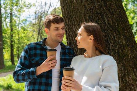 Photo pour Étudiants heureux tenant des tasses en papier et se regardant - image libre de droit