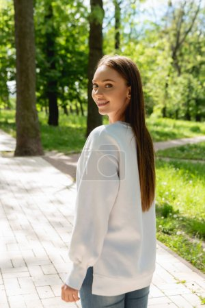 Photo for Cheerful girl in white sweatshirt standing in park and looking at camera - Royalty Free Image