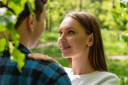 Photo for Selective focus of happy girl looking at boyfriend in park - Royalty Free Image