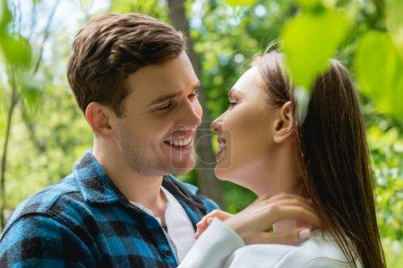 Photo pour Foyer sélectif de gaie fille et homme souriant se regardant dans le parc - image libre de droit