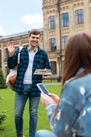 Photo pour Foyer sélectif de beau étudiant souriant tout en tenant des livres et en agitant la main près de la fille avec smartphone - image libre de droit