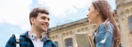 Photo pour Plan panoramique de fille gaie tenant des livres et parlant avec étudiant heureux - image libre de droit