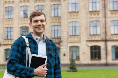 Photo pour Homme gai tenant tablette numérique avec écran blanc tout en se tenant près du campus universitaire - image libre de droit