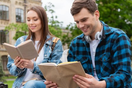 Photo pour Foyer sélectif de jeunes étudiants heureux et lisant des livres à l'extérieur - image libre de droit