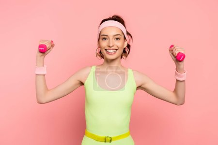 Photo for Cheerful sportswoman exercising with dumbbells on pink - Royalty Free Image