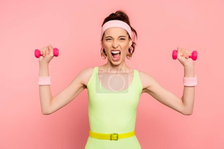 Photo for Emotional sportswoman looking at camera and exercising with dumbbells on pink - Royalty Free Image