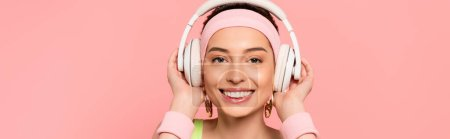 Photo for Horizontal image of cheerful girl touching headphones while listening music isolated on pink - Royalty Free Image