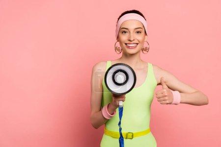 Photo pour Heureuse jeune femme montrant pouce levé et tenant haut-parleur sur rose - image libre de droit