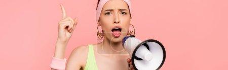Photo pour Concept horizontal de jeune femme émotionnelle pointant avec le doigt et tenant haut-parleur isolé sur rose - image libre de droit