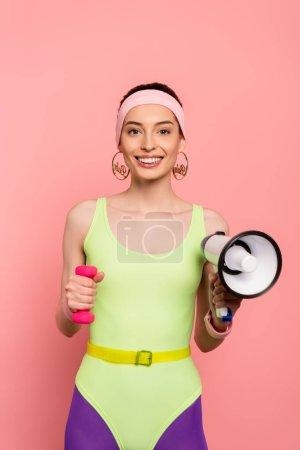 sportive gaie tenant haltère et haut-parleur sur rose