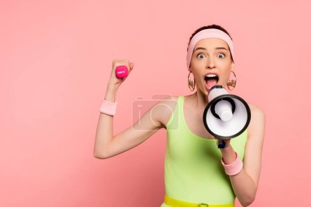 Photo for Emotional sportswoman holding loudspeaker and dumbbell while screaming on pink - Royalty Free Image