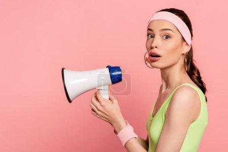 surpris jeune femme tenant haut-parleur isolé sur rose