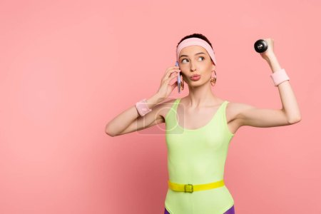 Photo for Sportswoman exercising and talking on smartphone on pink - Royalty Free Image