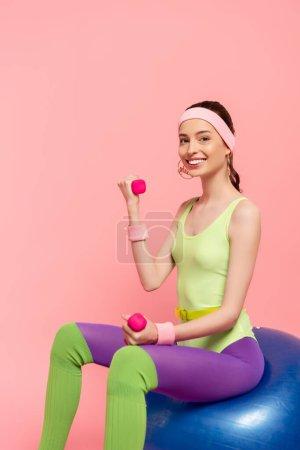 Photo pour Sportive souriante assise sur une balle de fitness et faisant de l'exercice avec des haltères isolées sur rose - image libre de droit