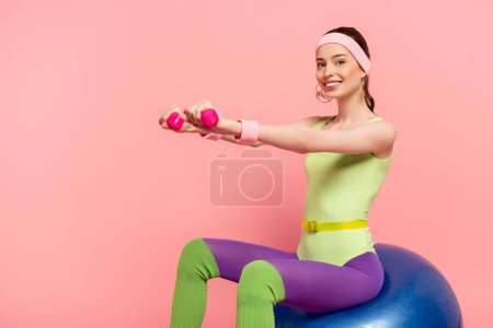 Photo for Smiling sportswoman with outstretched hands exercising with dumbbells and sitting on fitness ball on pink - Royalty Free Image