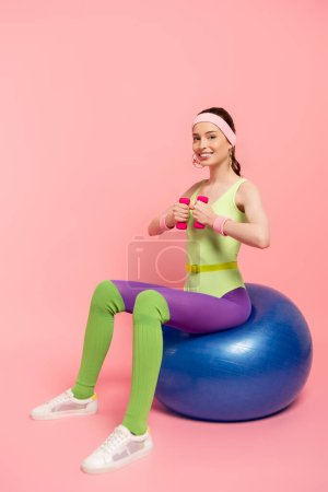 positive sportswoman exercising with dumbbells and sitting on fitness ball on pink