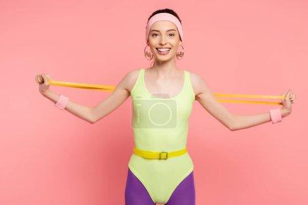 Photo pour Sportive heureuse faisant de l'exercice avec bande de résistance sur rose - image libre de droit