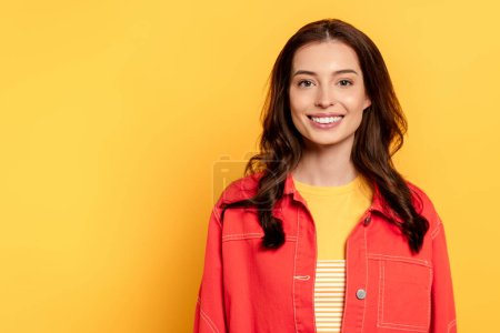 cheerful young woman standing and smiling on yellow