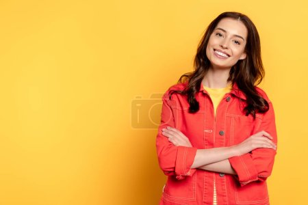 Photo pour Joyeuse jeune femme debout avec les bras croisés et souriant sur jaune - image libre de droit