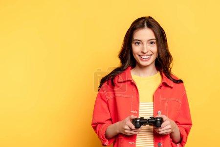 Photo pour KYIV, UKRAINE - 25 MAI 2020 : joyeuse jeune femme tenant un joystick et jouant au jeu vidéo sur jaune - image libre de droit
