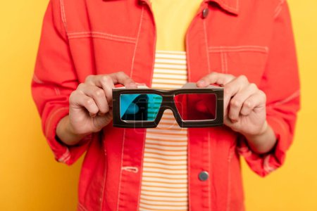 cropped view of woman holding 3d glasses isolated on yellow