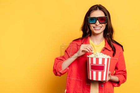 Photo pour Joyeuse jeune femme dans des lunettes 3d tenant seau de maïs soufflé sur jaune - image libre de droit