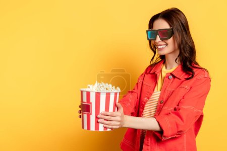 happy young woman in 3d glasses looking at popcorn bucket on yellow