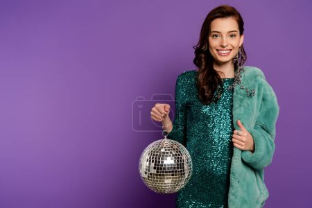Photo for Cheerful and stylish woman holding disco ball and showing thumb up on purple - Royalty Free Image