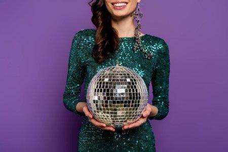 Photo pour Vue recadrée de jeune femme heureuse en robe tenant boule disco sur violet - image libre de droit