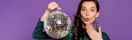 Photo pour Concept panoramique de jeune femme surprise tenant le ballon disco isolé sur violet - image libre de droit