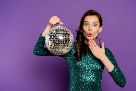Photo pour Surpris jeune femme en robe tenant boule disco sur violet - image libre de droit
