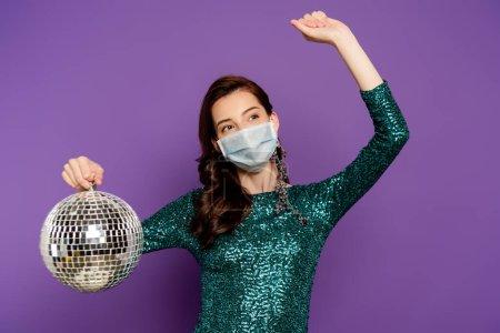Photo pour Femme en robe et masque médical tenant boule disco sur violet - image libre de droit