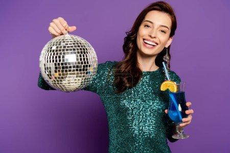 Photo pour Femme heureuse en robe tenant boule disco et cocktail en verre sur violet - image libre de droit