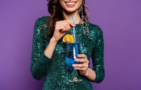 Photo pour Vue recadrée de femme gaie en robe de soirée tenant cocktail d'alcool et de paille sur violet - image libre de droit