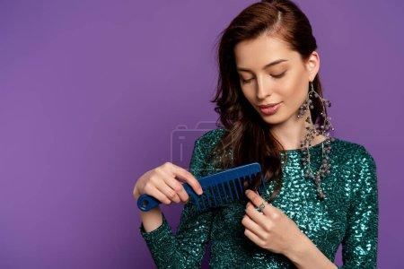 Photo pour Belle femme en robe tenant peigne et brossant les cheveux isolés sur violet - image libre de droit