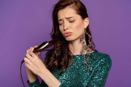 mujer disgustado sosteniendo alisador de pelo pequeño cerca de pelo brillante aislado en púrpura