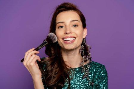 Photo pour Femme gaie tenant pinceau cosmétique tout en appliquant blush isolé sur violet - image libre de droit