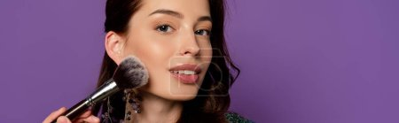 Photo for Horizontal concept of young woman holding cosmetic brush while applying blush isolated on purple - Royalty Free Image