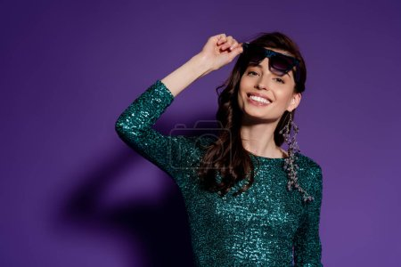 Photo for Happy woman touching sunglasses and smiling on purple - Royalty Free Image