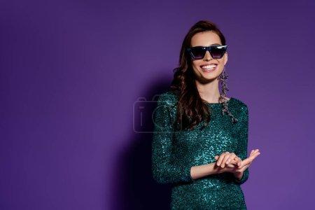 Photo pour Femme souriante dans des lunettes de soleil debout sur violet - image libre de droit