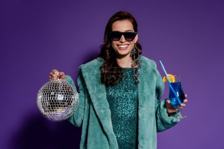 Photo for Happy woman in sunglasses smiling while holding glass with cocktail and disco ball on purple - Royalty Free Image