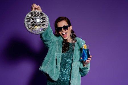 Photo pour Femme heureuse dans des lunettes de soleil tenant verre avec cocktail et boule disco sur violet - image libre de droit