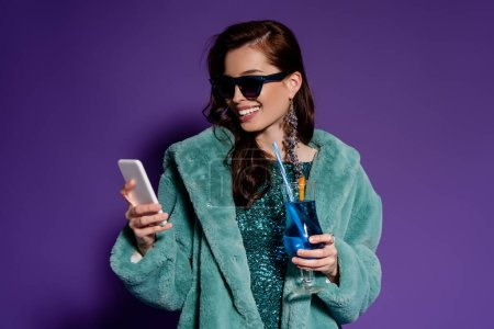 Photo for Happy woman in sunglasses holding glass with cocktail and smartphone on purple - Royalty Free Image