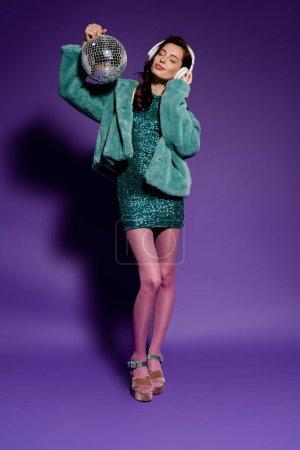 Photo pour Femme heureuse en robe de soirée touchant écouteurs et tenant boule disco sur violet - image libre de droit