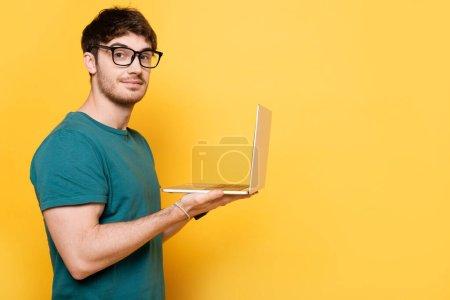 Photo pour Sourire jeune homme regardant la caméra tout en tenant un ordinateur portable sur jaune - image libre de droit