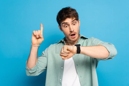 Photo for Shocked young man showing idea gesture while looking at wristwatch on blue - Royalty Free Image