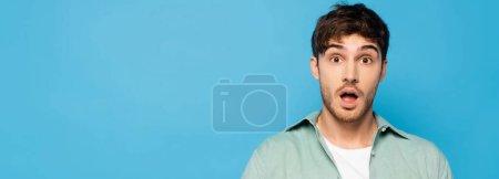 Photo pour Image horizontale d'un jeune homme choqué regardant une caméra isolée sur bleu - image libre de droit