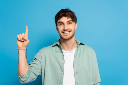 Photo for Happy man looking at camera while showing idea gesture on blue - Royalty Free Image